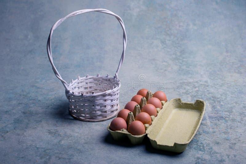 Een karton van dozijn verse eieren en witte mand stock foto