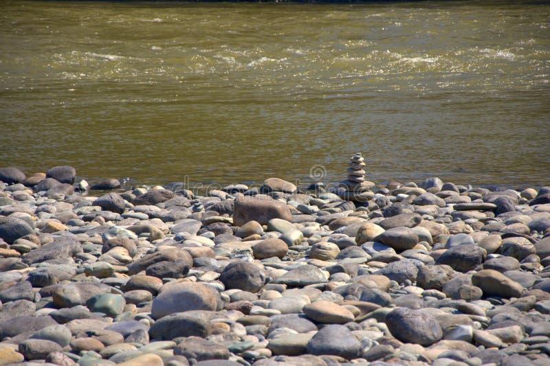 Een keipiramide op de rotsachtige kust van de vlugge bergrivier wordt geassembleerd Katun die royalty-vrije stock foto