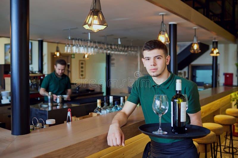 Een kelner die een dienblad met fles wijn en glazen in bar houden royalty-vrije stock afbeelding