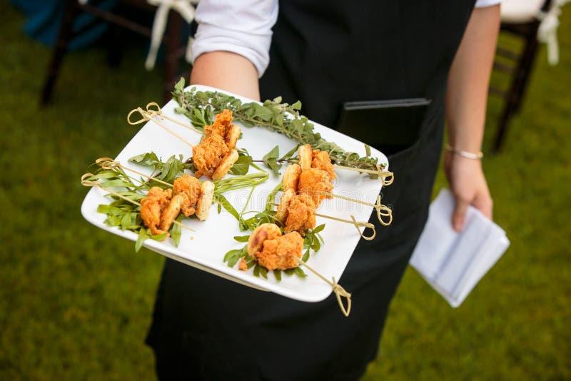 Een kelner die een plaat van mini gebraden kip en wafels houden - de reeks van de huwelijkscatering stock afbeelding