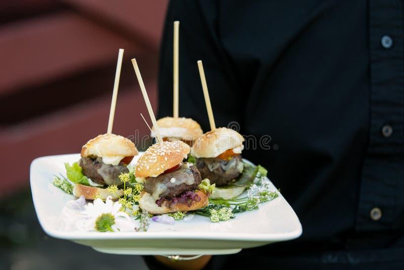 Een kelner die een schotel van minihamburgers houden - de reeks van de huwelijkscatering stock afbeelding