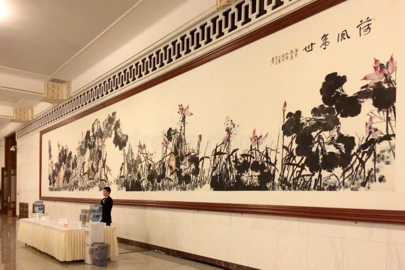 Een kelner die zich voor het Chinese schilderen in de Grote Zaal van Mensen in Peking bevinden royalty-vrije stock foto's