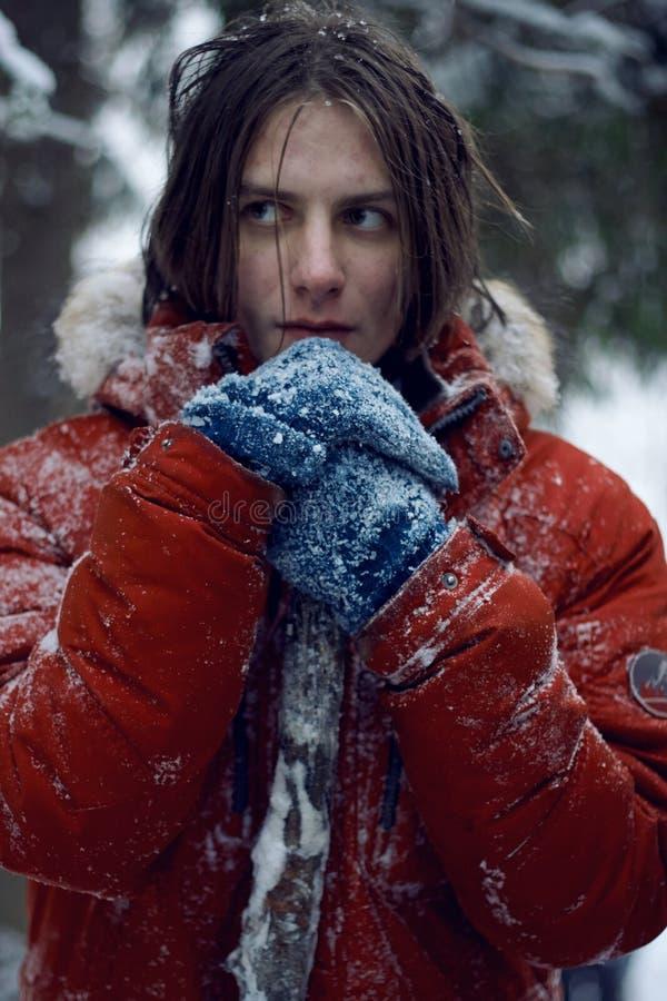 Een kerel bevindt zich in een ijzig snow-covered bos stock fotografie