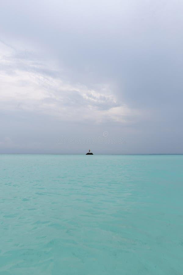 Een kerel bevindt zich op een rots in het midden van de oceaan De macht van de oceaan royalty-vrije stock foto