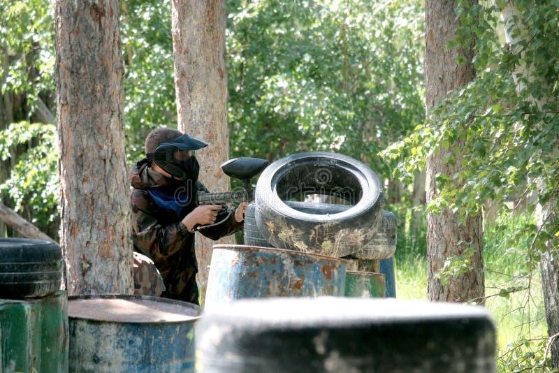 Een kerel in camouflagekleren van een blauw team met wapens in zijn handen gluurt uit van achter een ijzervat en banden Het spel  stock afbeeldingen