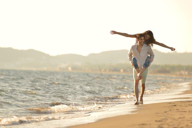 Een kerel die een meisje op zijn rug vervoeren, bij het strand, in openlucht royalty-vrije stock foto