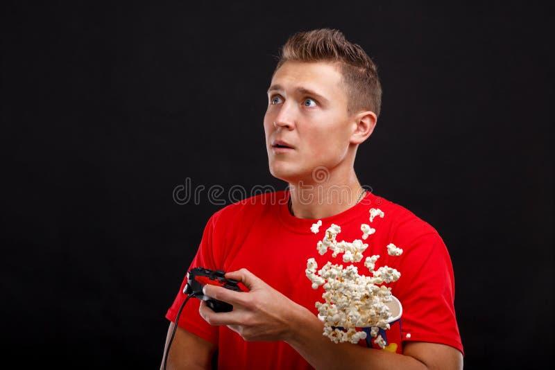 Een kerel die een glas met verspreide popcorn en een spelbedieningshendel houden en omhoog in verrassing kijken Zwarte achtergron stock fotografie