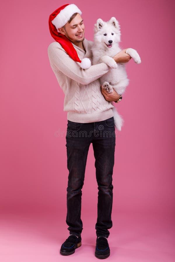 Een kerel die een hond op een roze achtergrond houden royalty-vrije stock foto's