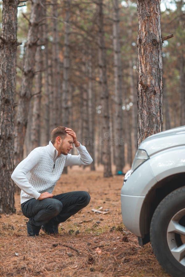 Een kerel die, die naast een gebroken auto hurken en gek hoofd houden in het de herfstbos stock fotografie