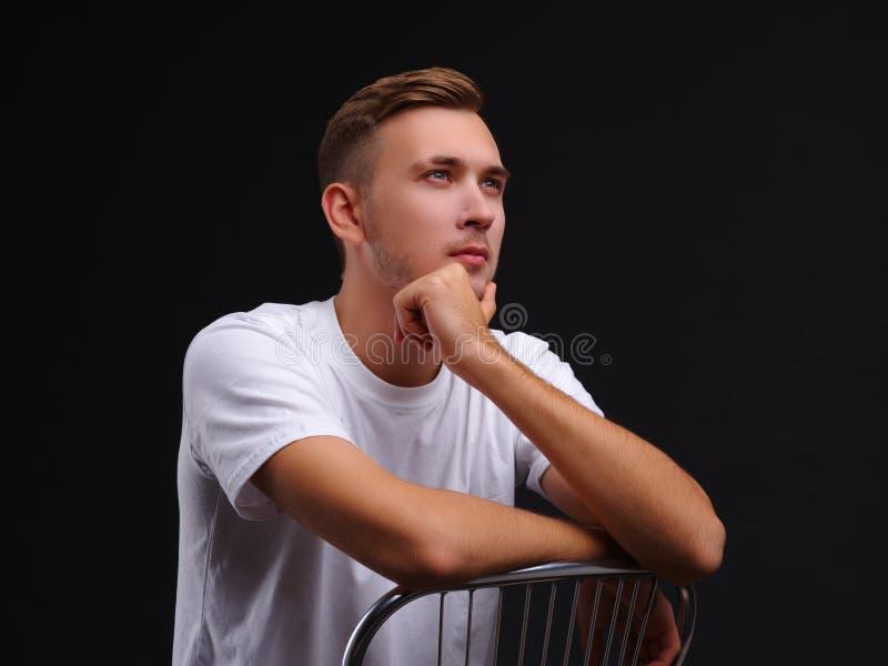 Een kerel die, die op een stoel zitten en in de afstand met ernstige peinzend staren ziet eruit royalty-vrije stock foto