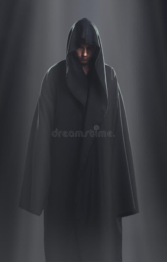 Een kerel in een zwarte robe die zich in dark bevinden stock afbeelding
