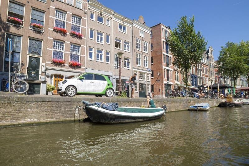 Een kerel en een meisje bereiden een boot voor het varen op de kanalen van Amsterdam voor stock fotografie