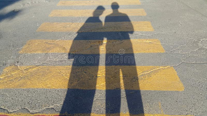 Een kerel en een meisje bevinden zich aan het begin van een voetgangersoversteekplaats, waar het einde wordt geschreven en wachte royalty-vrije stock fotografie