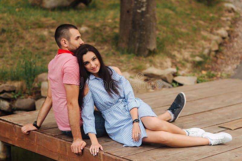 Een kerel en een meisje genieten van elkaar in een romantische atmosfeer, zitten op de pijler royalty-vrije stock foto