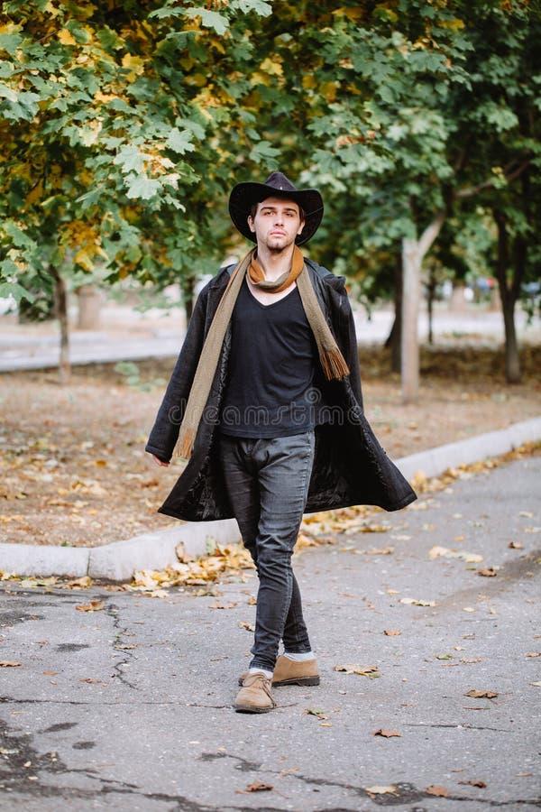 Een kerel in een hoed en een laag gaat onderaan de straat outdoors stock afbeeldingen