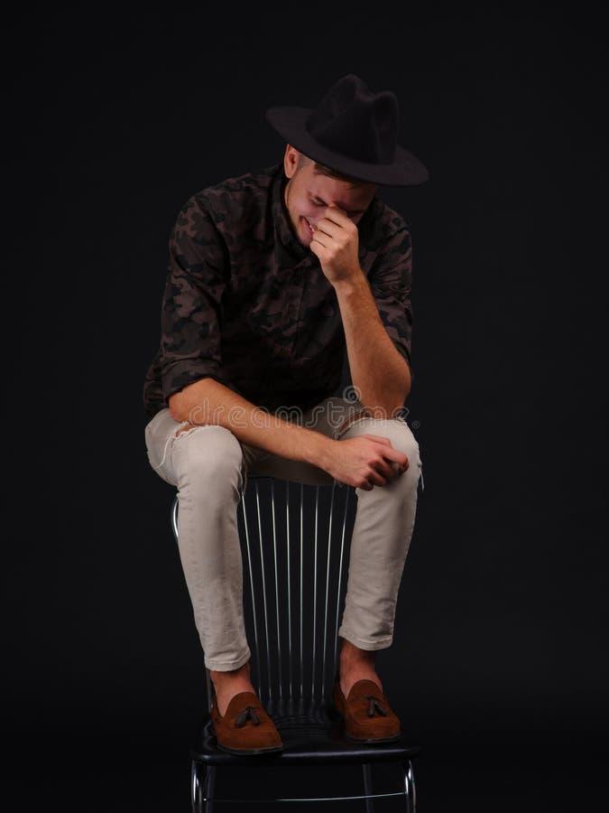 Een kerel in een hoed zit bovenop een stoel, lacht en behandelt zijn gezicht met overgeheld hoofd royalty-vrije stock foto's
