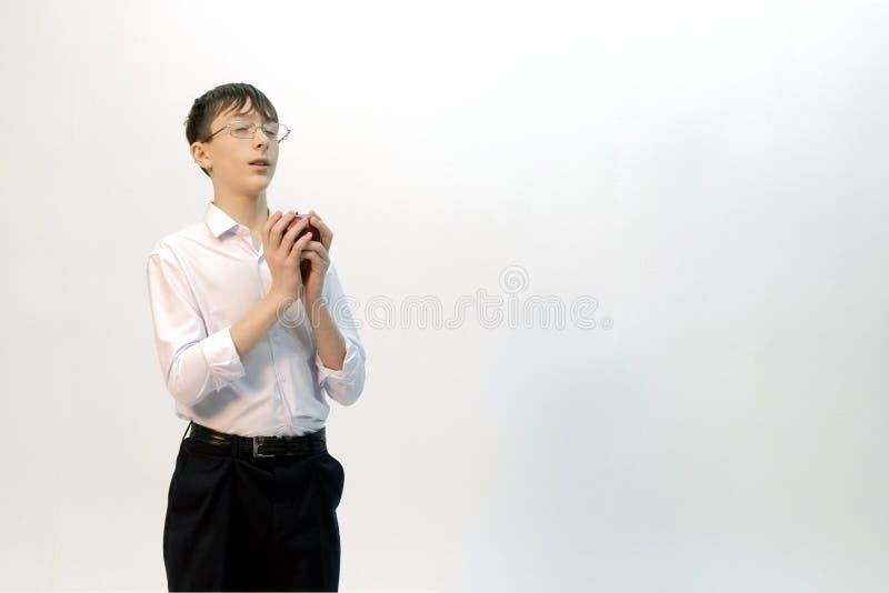 Een kerel met glazen met zijn gesloten ogen houdt een appel in zijn handen en droomt over iets Witte achtergrond exemplaar royalty-vrije stock foto's
