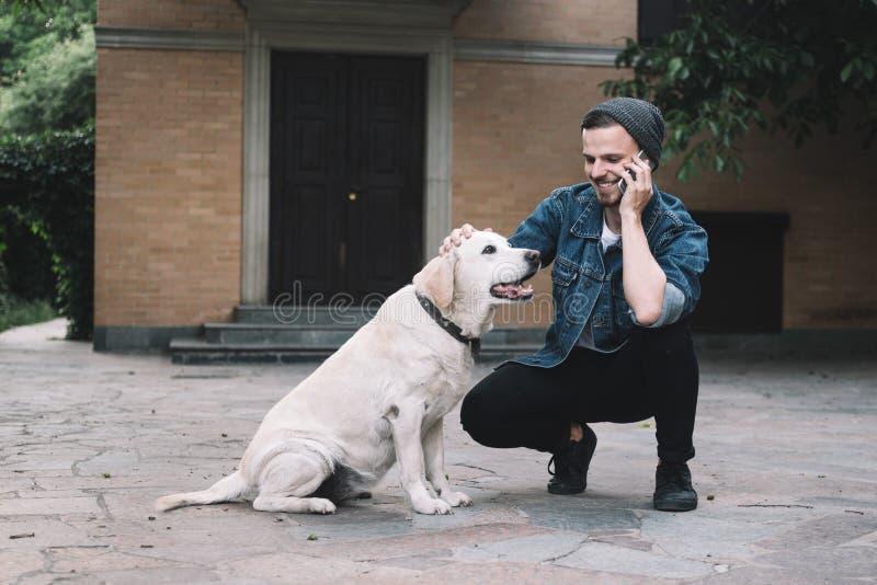 Een kerel met een hond stock afbeeldingen