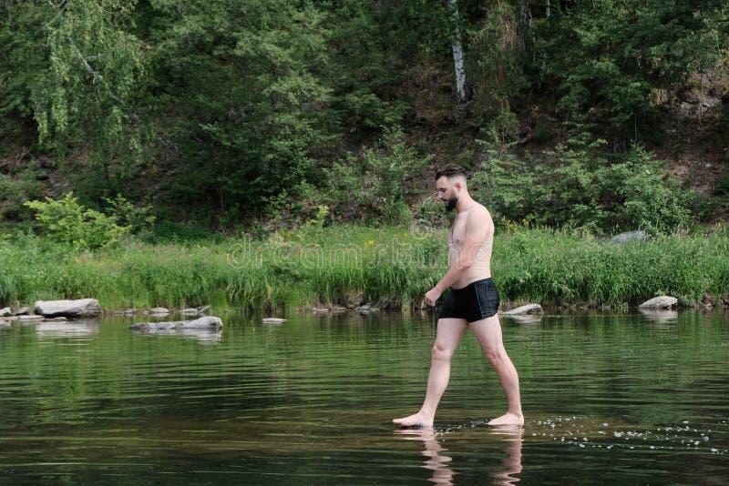Een kerel met een Kaukasisch-Typebaard loopt langs de oppervlakte van het water in een rivier of een meer in een bos het concept  stock fotografie