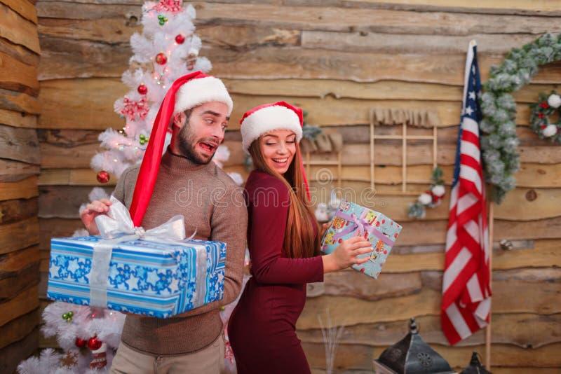 Een kerel met een meisje die zich met hun ruggen tegen de achtergrond van een Kerstboom bevinden stock fotografie