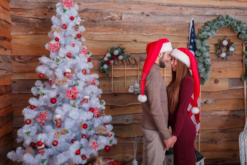 Een kerel met een meisje met glimlachen in Nieuwjaar` s hoeden staat gereed en het houden dient een houten ruimte in stock afbeelding