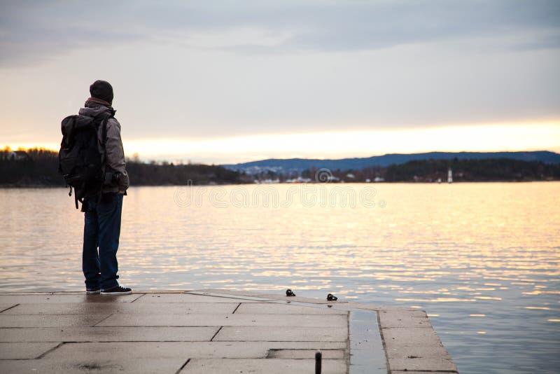 Een kerel met rugzak kijkt over het overzees en het dromen van het reizen royalty-vrije stock afbeelding