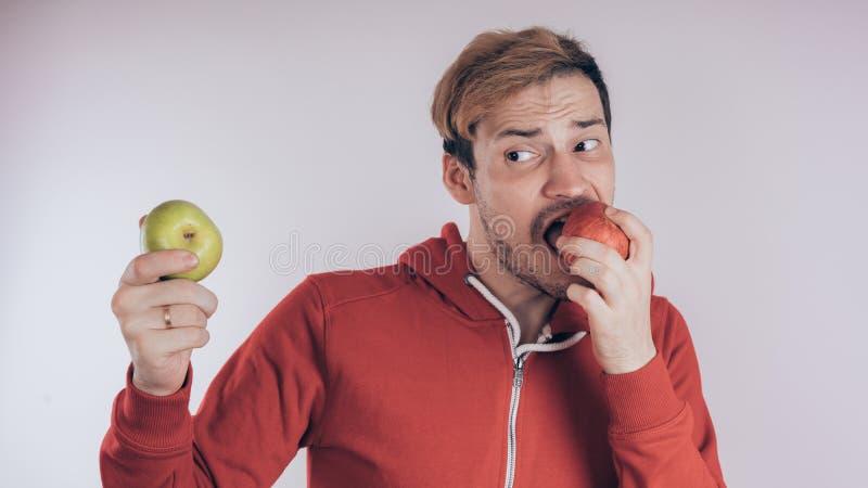 Een kerel met een vrolijk gezicht houdt groen Apple en groen Apple, op een witte achtergrond Het concept liefde van gezond voedse royalty-vrije stock afbeeldingen