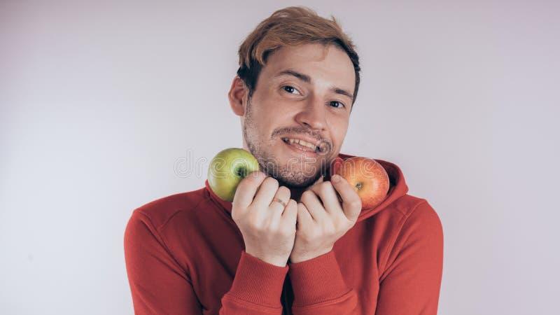 Een kerel met een vrolijk gezicht houdt groen Apple en groen Apple, op een witte achtergrond Het concept liefde van gezond voedse stock fotografie
