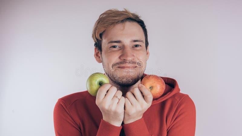 Een kerel met een vrolijk gezicht houdt groen Apple en groen Apple, op een witte achtergrond Het concept liefde van gezond voedse royalty-vrije stock afbeelding