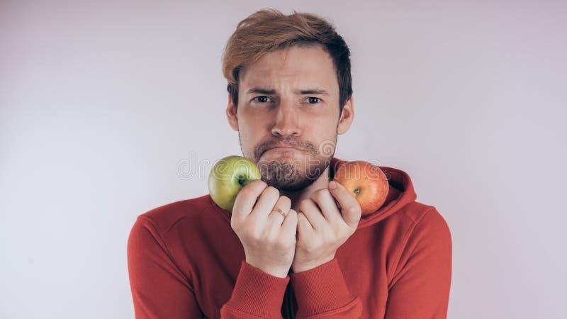 Een kerel met een vrolijk gezicht houdt groen Apple en groen Apple, op een witte achtergrond Het concept liefde van gezond voedse stock foto