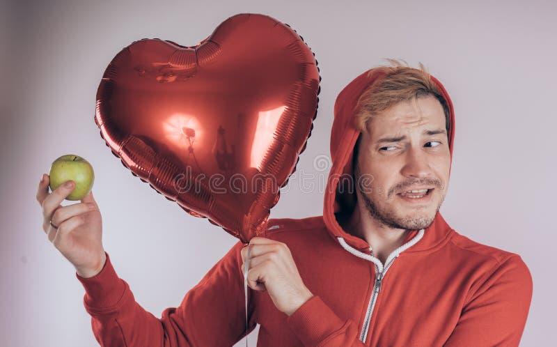 Een kerel met een vrolijk gezicht houdt groen Apple en een rode hart-vormige ballon, op een witte achtergrond Het concept liefde  stock afbeelding