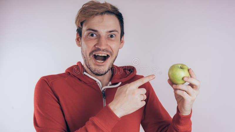 Een kerel met een vrolijk gezicht houdt groen Apple, op een witte achtergrond Het concept liefde van gezond voedsel royalty-vrije stock fotografie