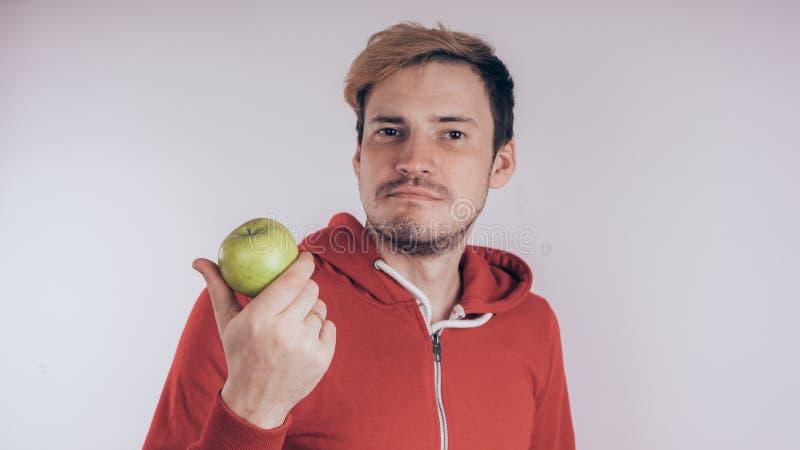 Een kerel met een vrolijk gezicht houdt groen Apple, op een witte achtergrond Het concept liefde van gezond voedsel stock foto