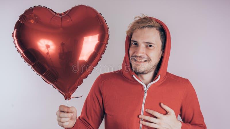 Een kerel met een vrolijk gezicht houdt een rode hart-vormige ballon, op een witte achtergrond royalty-vrije stock foto