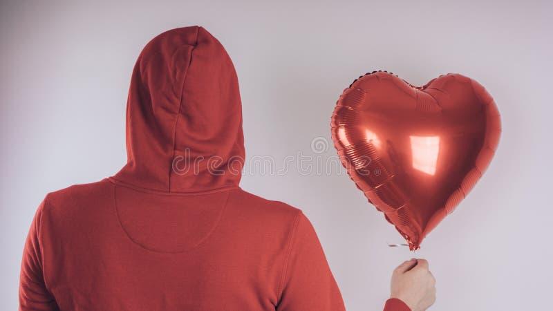 Een kerel met een vrolijk gezicht houdt een rode hart-vormige ballon, op een witte achtergrond stock afbeeldingen