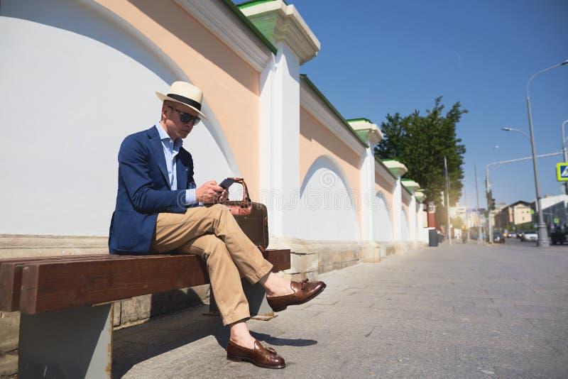 een kerel in een pakzitting op een bank en het spreken op de telefoon royalty-vrije stock foto's