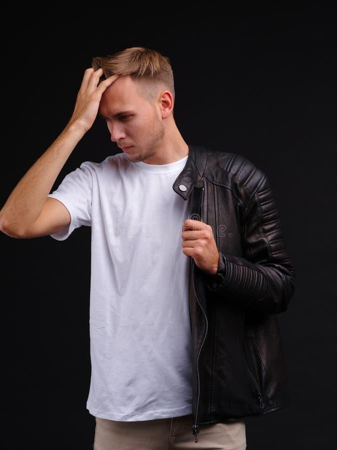 Een kerel in een T-shirt en half gekleed in een jasje en de blikken neer met een ernstige blik en maken zijn haar recht stock foto