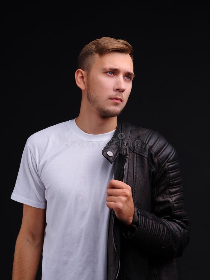 Een kerel in een T-shirt en half gekleed in een leerjasje en blikken weg met een het doordringen starende blik royalty-vrije stock afbeeldingen