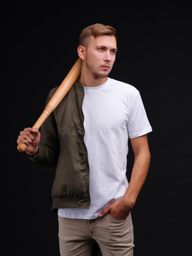 Een kerel in een T-shirt en een windjekker, die een houten knuppel op zijn schouder houden royalty-vrije stock afbeeldingen