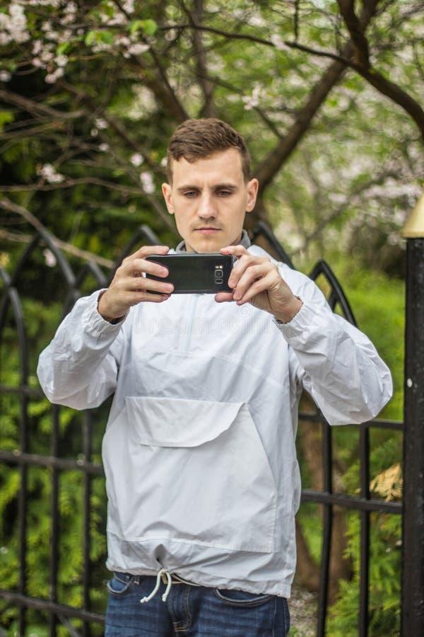 Een kerel van Europese verschijningsfoto's op een telefoon stock fotografie
