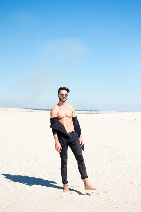 Een kerel werpt zand op het zand op een hete de zomerdag royalty-vrije stock fotografie