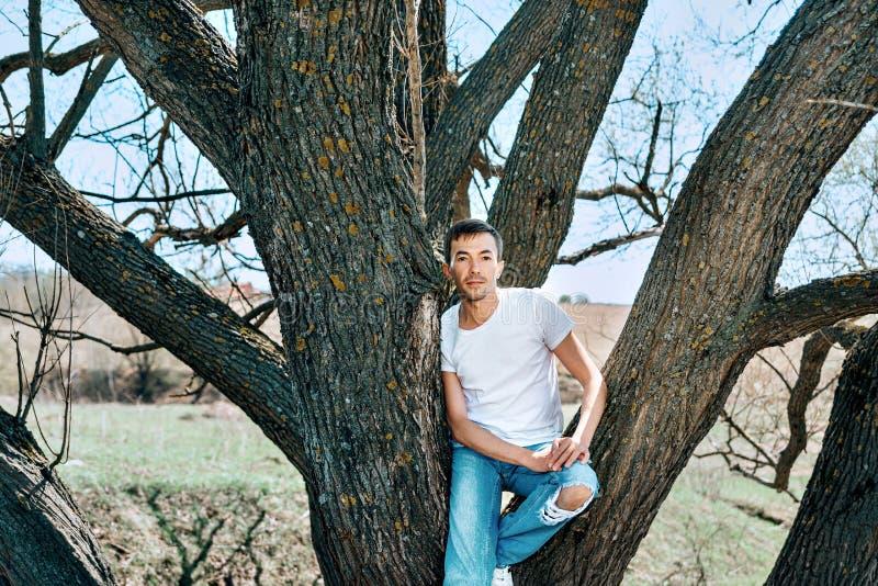 Een kerel in een witte T-shirt en jeans zit tussen de bomen royalty-vrije stock afbeelding