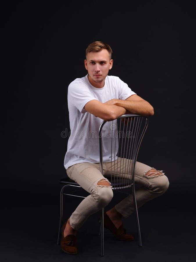 Een kerel in een witte T-shirt zit op een stoel Op een zwarte achtergrond royalty-vrije stock afbeelding