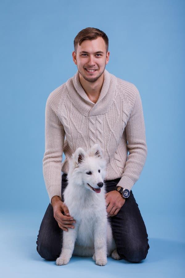 Een kerel zit naast een Samoyed-puppy Op een blauwe achtergrond stock fotografie