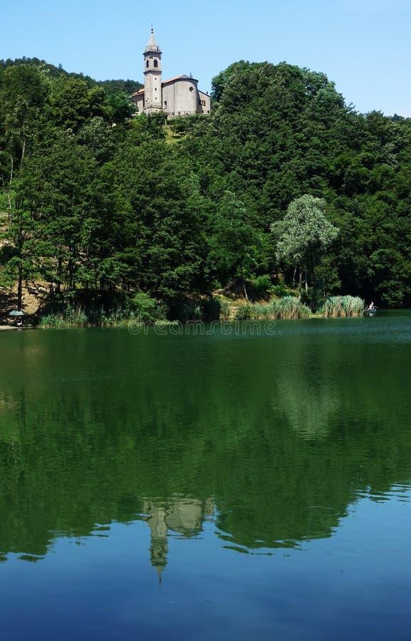 Een kerk met zijn klokketoren overdenkt het meer van Castel-dell ` Alpi royalty-vrije stock afbeeldingen