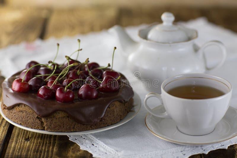 Een kersenpastei, met verse kersen een kop thee en een ketel royalty-vrije stock afbeelding