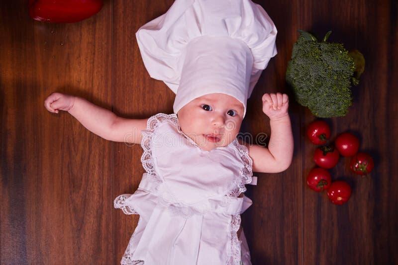 Een kind, baby, meisje, ligt op de keukenlijst, in GLB van een kok en in een schort, naast hem zijn groenten, broccoli, tomaten, royalty-vrije stock foto