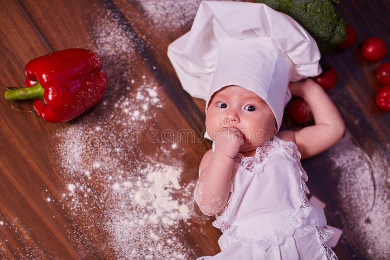 Een kind, baby, meisje, ligt op de keukenlijst, in GLB van een kok en in een schort, in witte sokken, naast bloem, groenten, pepp stock foto's