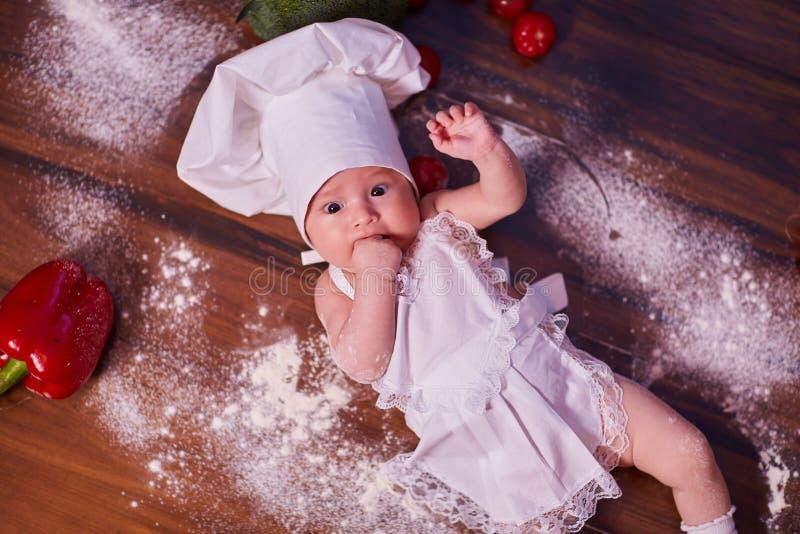 Een kind, baby, meisje, ligt op de keukenlijst, in GLB van een kok en in een schort, in witte sokken, naast bloem, groenten, pepp royalty-vrije stock foto's
