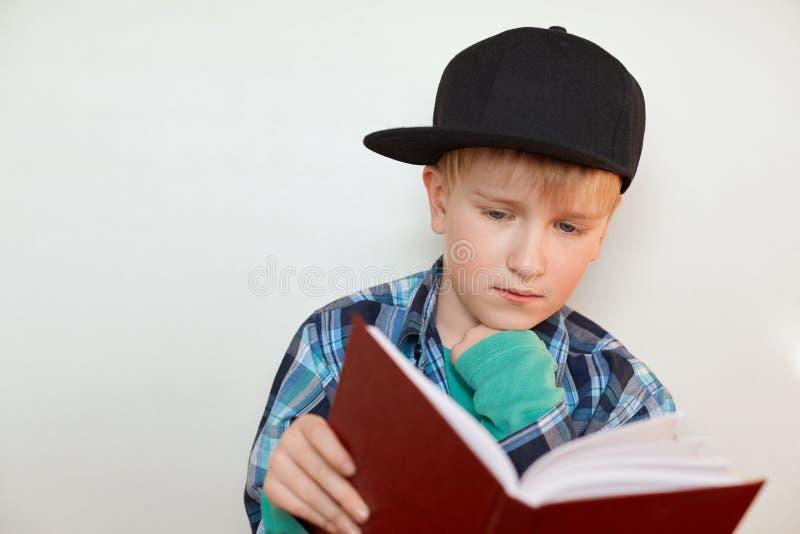 Een kind die van lage schoolleeftijd thuiswerk doen De jongen in GLB met blond haar en blauwe ogen doet zijn thuiswerk die een bo royalty-vrije stock afbeelding